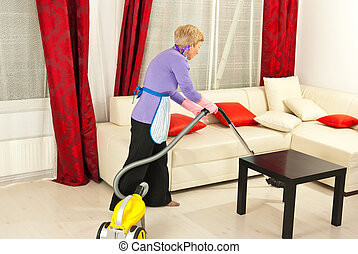 Woman cleaning room with vacuum - Senior woman cleaning home...