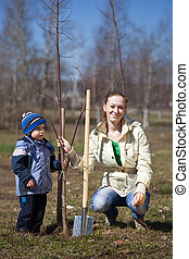 woman and boy planting tree - woman and boy with spade...