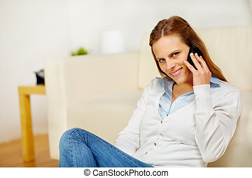 Beautiful woman speaking on cellphone at home