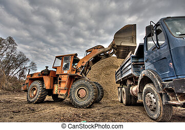 excavator loading gravel into a truck