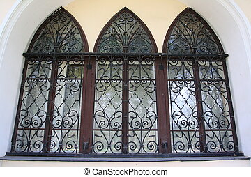 Old arched window with metal grating
