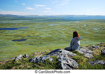 Woman against the green tableland with many small lakes - A...