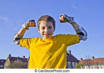smiling teenage boy in roller-blading protection kit...