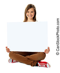 Smiling pretty teenager posing with blank placard, seated on...