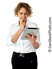 Businesswoman looking at tablet and thinking deep Lost in...