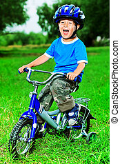 emotional kid - Happy boy on a bicycle in a summer park