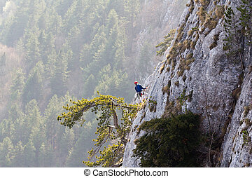 Mountain climber - A mountain climber looking down, keeping...