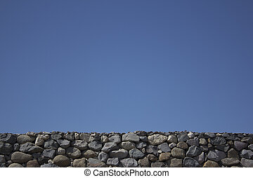 Blue sky with rock boulder wall - Rock boulder wall with a...