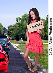Woman Hitch Hiking to a Concert - A beautiful woman with a...