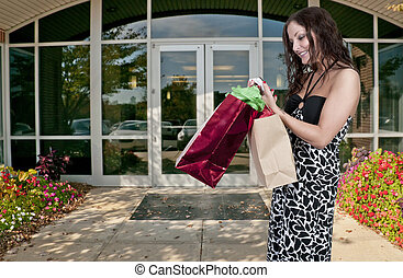 Woman Shopping Bags - A beautiful young woman texting while...