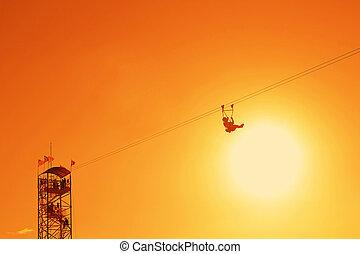 man in silhouette enjoying the ride at zipline