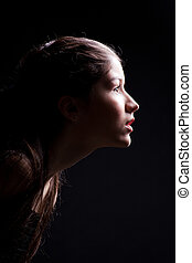 young girl lasting forward to light on black - Close up...