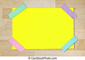 yellow blank paper stuck with colorful tape on wood wall