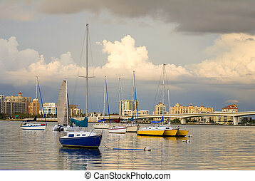Boats in Harbor Under Cloudy Skies - Boats anchored in a...