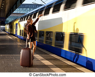 young lady with luggage stop a train