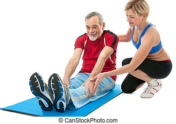Senior man doing fitness exercise with help of trainer at...