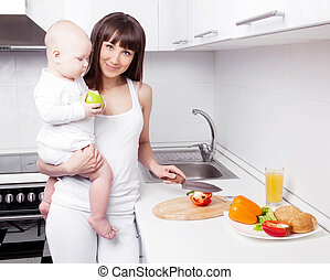 woman with baby cooking - beautiful young woman holding her...