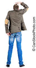 Back view of thinking business man in jacket .
