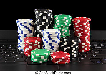 poker chips on keyboard - stack of casino gambling chips on...