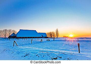 Sunset of farm in winter landscape