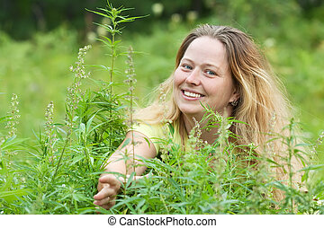 Happy woman with fresh hemp    at cannabis plant