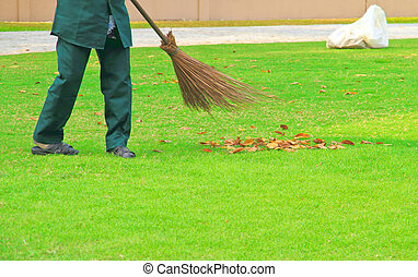 woman worker sweeping leaves on grass