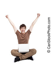 Happy young man using laptop on the floor isolated on white background