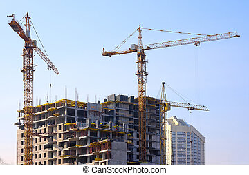 Building cranes and under construction building against the...