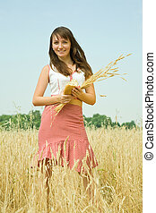 Girl with bread and wheat ears at field in summer