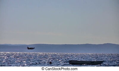 Airplane flying over sea and small boat at anchor