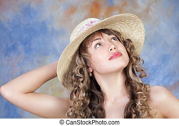 portrait of a cute young woman wearing a straw hat