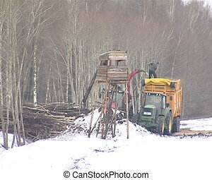 granulated chips fall - tractor with crane loads branches to...