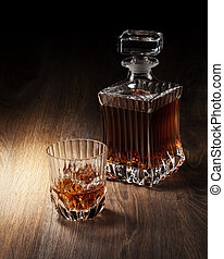 glass and bottle with whiskey on a woden table