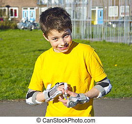 smiling teenage boy in roller-blading protection kit -...