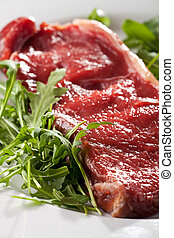 raw loin steak on rocket salad