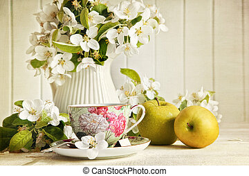 Tea cup with flower blossoms and green apples - Tea cup with...
