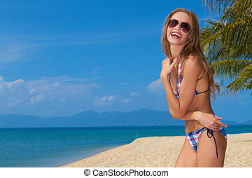 Smiling woman with sunglasses on sandy beach