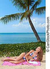 Woman reading on a tropical beach - Beautiful blonde woman...