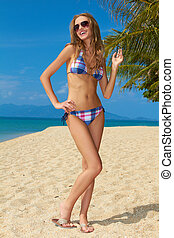 Attractive woman with sunglasses on sandy beach