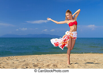 Adorable woman standing at the tropical beach, wearing...