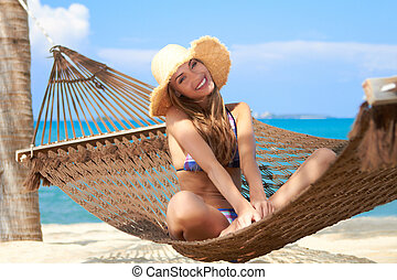 Woman with lovely smile sitting in a hammock - Gentle...
