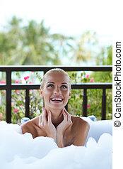 Smiling woman enjoying a foamy bubble bath - Pretty smiling...