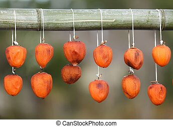 dried kaki fruit hanging from a bamboo stick, Japan