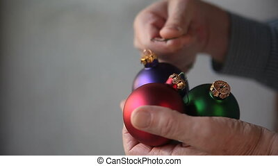man with Christmas ornaments - a man attaches hangers to...