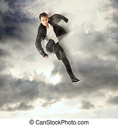 Cool young man jumping and kicking in the cloudy sky