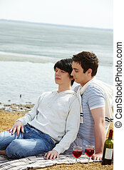 Togetherness - Gay couple resting at beach, boy leaning...