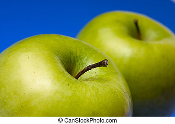 appetizing apples of green color on a blue background