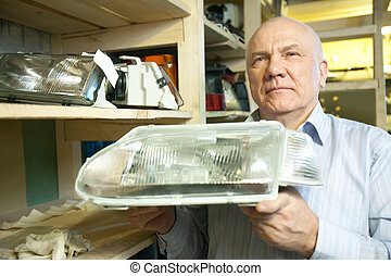 mature man holds automotive headlight in auto parts store...
