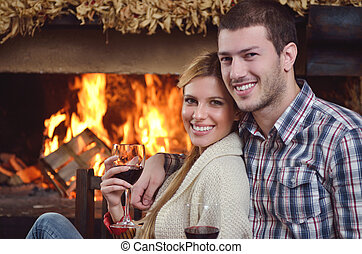 Young romantic couple sitting and relaxing in front of...