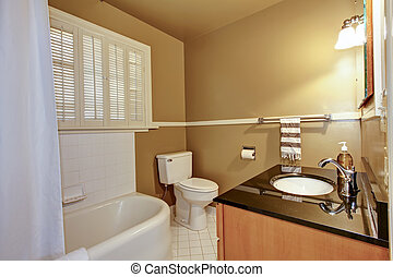 Old brown bathroom with white tub. - Old brown bathroom with...